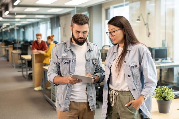 Joven empresario seguro apuntando a la pantalla táctil mientras hace la presentación de algunas ideas a su colega asiática