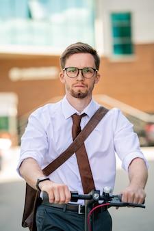 Joven empresario serio en anteojos y ropa formal yendo a casa en bicicleta mientras avanza al aire libre