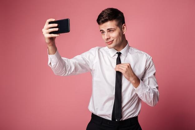 Joven empresario serio hacer selfie por teléfono móvil