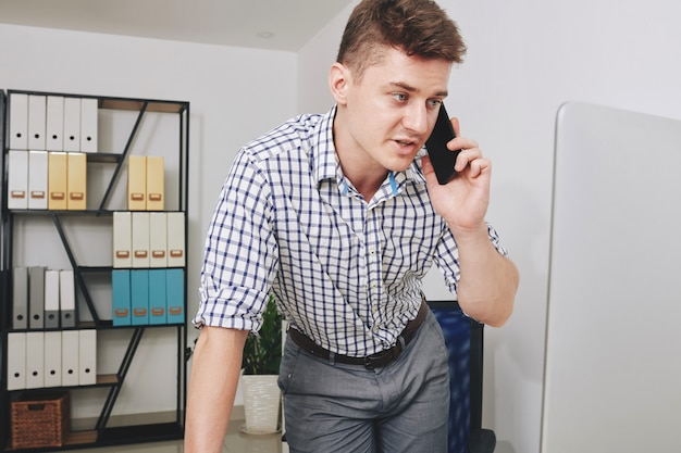 Joven empresario serio mirando la pantalla de la computadora y llamando por teléfono con el cliente o compañero de trabajo
