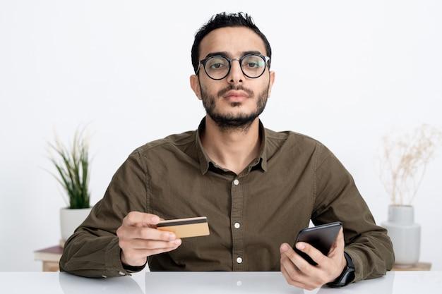 Joven empresario serio con tarjeta de crédito y teléfono inteligente que va a realizar el pago de los productos que ordenó a través de internet.