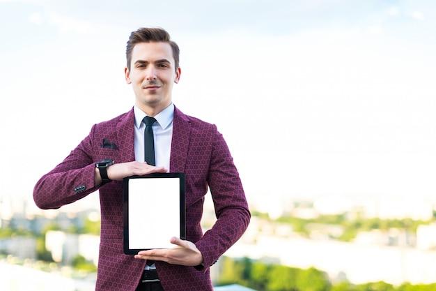 Joven empresario serio en traje rojo y camisa con corbata de pie en el techo con tableta vacía