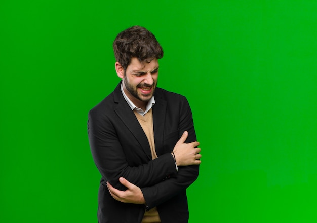 Joven empresario se siente ansioso, enfermo, enfermo e infeliz, sufriendo dolor de estómago o gripe contra la pared verde