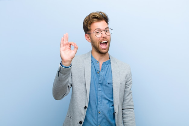 Joven empresario se siente exitoso y satisfecho, sonriendo con la boca abierta, haciendo un signo bien con la mano