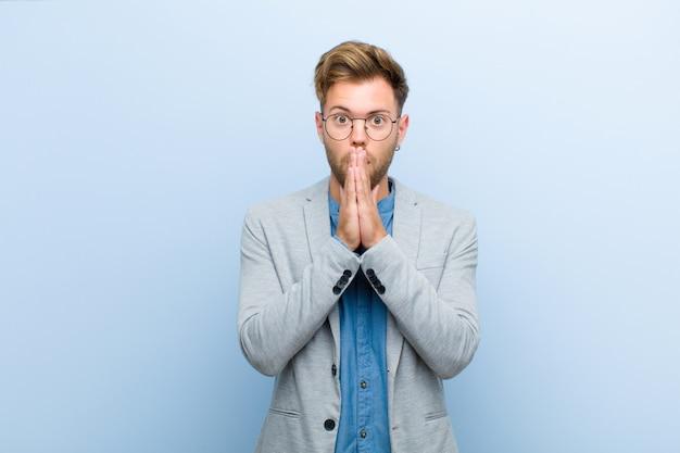Joven empresario se siente preocupado, molesto y asustado, cubriéndose la boca con las manos, luciendo ansioso y confundido con el fondo azul