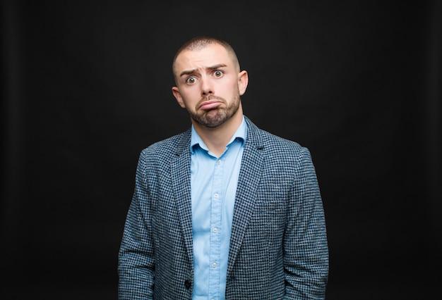 Joven empresario se siente triste y llorón con una mirada infeliz, llorando con una actitud negativa y frustrada contra la pared plana