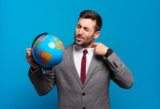 Joven empresario sintiéndose estresado, ansioso, cansado y frustrado, tirando del cuello de la camisa, luciendo frustrado con el problema de sostener un mapa del globo terráqueo