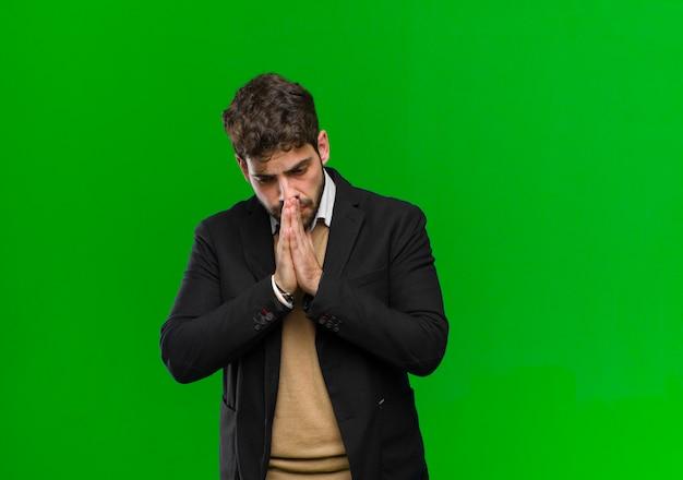 Joven empresario sintiéndose preocupado, esperanzado y religioso, rezando fielmente con las palmas presionadas, pidiendo perdón verde