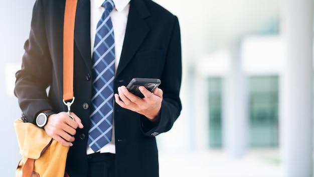 Joven empresario en smartphone caminando en la calle usando la aplicación de mensajes de texto en el teléfono inteligente.