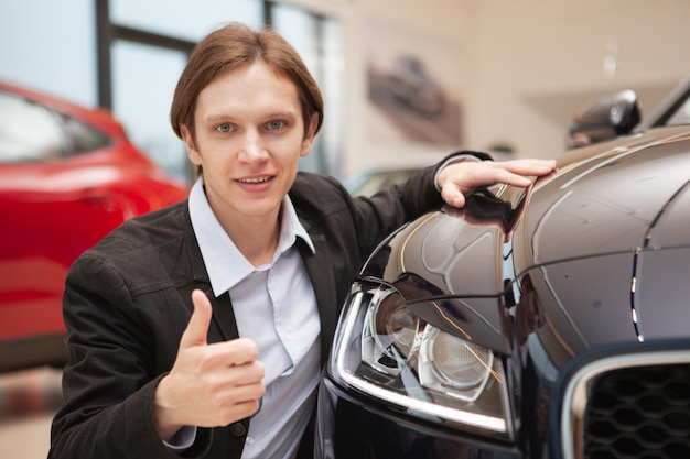 Joven empresario sonriendo, mostrando los pulgares hacia arriba mientras elige un coche nuevo para comprar en el salón del concesionario, copie el espacio