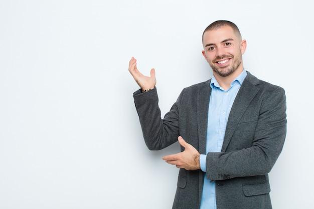 Joven empresario sonriendo con orgullo y confianza, sintiéndose feliz y satisfecho y mostrando un concepto de espacio de copia contra la pared plana
