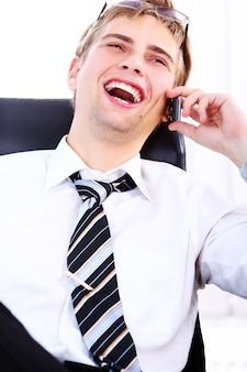 Joven empresario sonriente con teléfono celular