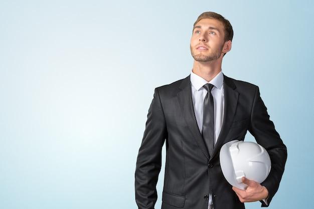 Joven empresario sosteniendo casco blanco