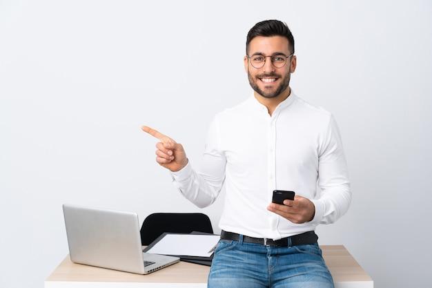 Joven empresario sosteniendo un teléfono móvil apuntando con el dedo al lado