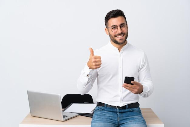 Joven empresario sosteniendo un teléfono móvil dando un gesto de pulgares arriba