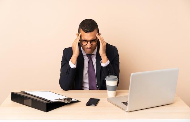 Joven empresario en su oficina con una computadora portátil y otros documentos con dolor de cabeza