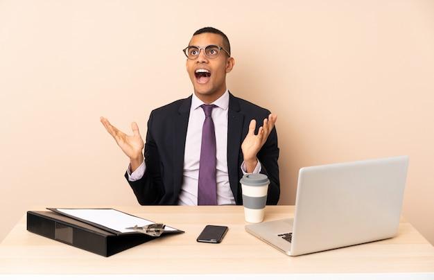 Joven empresario en su oficina con una computadora portátil y otros documentos con expresión facial sorpresa
