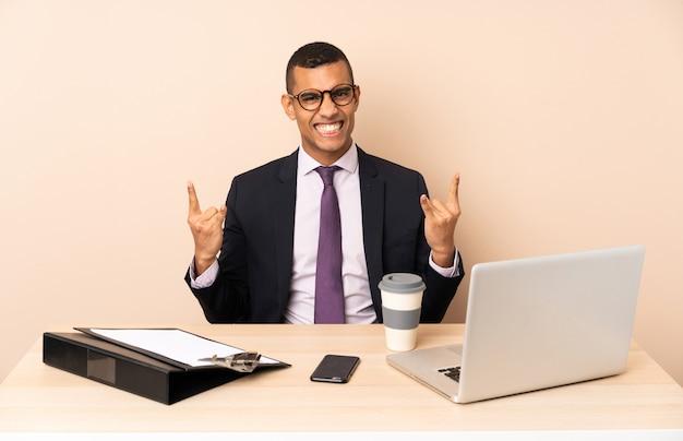 Joven empresario en su oficina con una computadora portátil y otros documentos haciendo gesto de rock