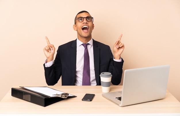 Joven empresario en su oficina con una computadora portátil y otros documentos sorprendidos y apuntando hacia arriba