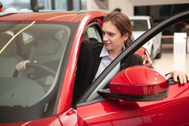 Joven empresario subiendo al coche en el concesionario de automóviles