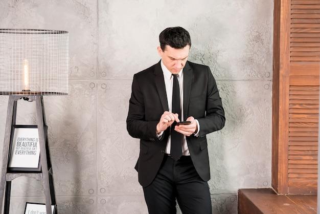 Joven empresario con teléfono inteligente de pie por la pared