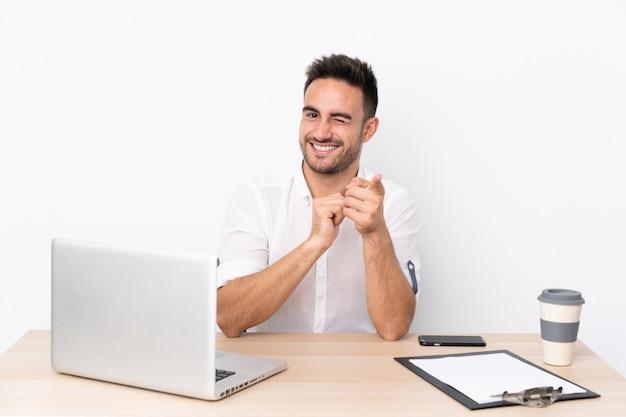 Joven empresario con un teléfono móvil en un lugar de trabajo le señala con el dedo