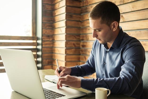 Joven empresario tomando notas de su computadora portátil