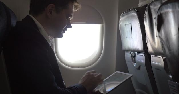 Joven empresario trabajando con almohadilla en avión