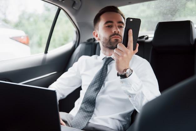 Un joven empresario trabajando en la computadora portátil y hablando por teléfono mientras está sentado en la parte trasera del coche. trabaja en movimiento, aprecia su tiempo
