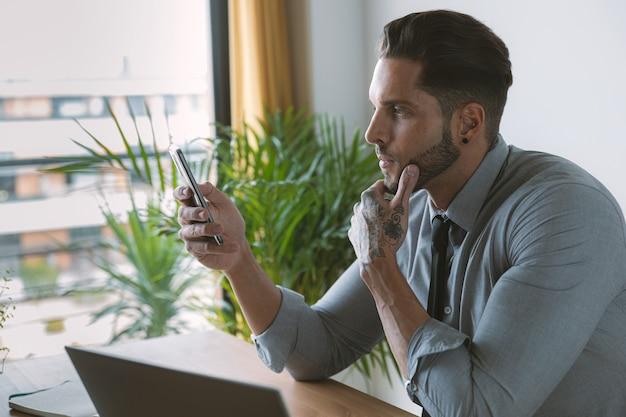 Joven empresario trabajando en la computadora portátil mientras revisa el teléfono