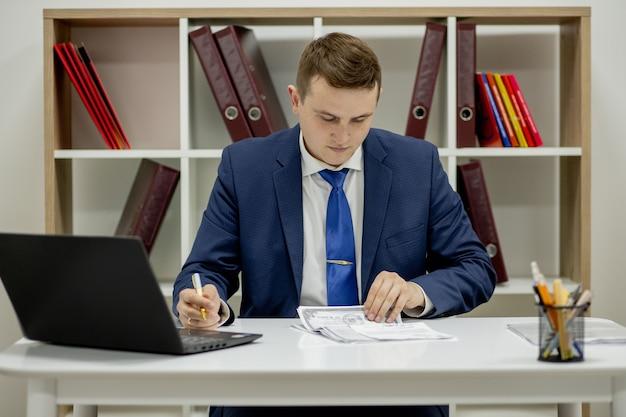 Joven empresario trabajando con documentos mirando documentos en carpeta, sentado en el escritorio de oficina.