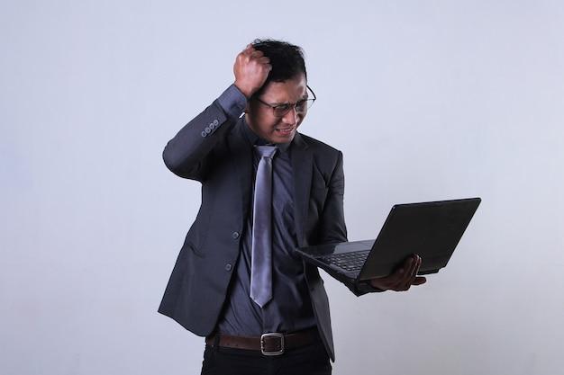 Joven empresario trabajando en equipo portátil y parece frustrado