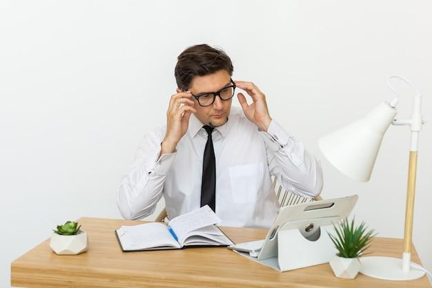 Joven empresario trabajando en oficina, sentado en el escritorio