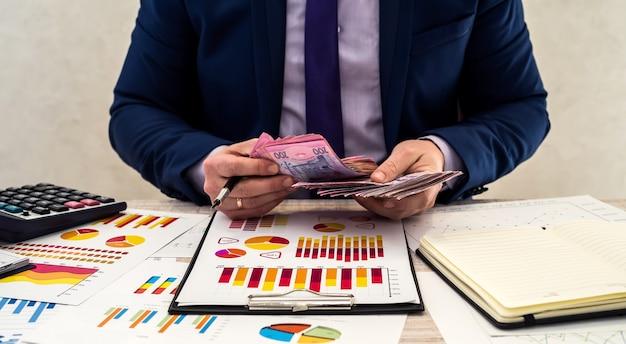 Joven empresario en traje cuenta dinero hryvnia y trabaja con gráficos y documentos como ingreso mensual neto. el concepto de dinero es salario o corrupción. trabaja en la oficina.