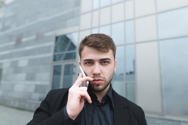 Joven empresario en un traje hablando por teléfono