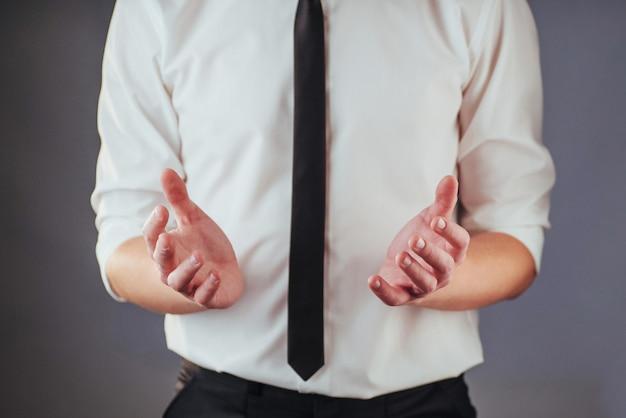 El joven empresario en un traje muestra su mano sobre un fondo oscuro aislado