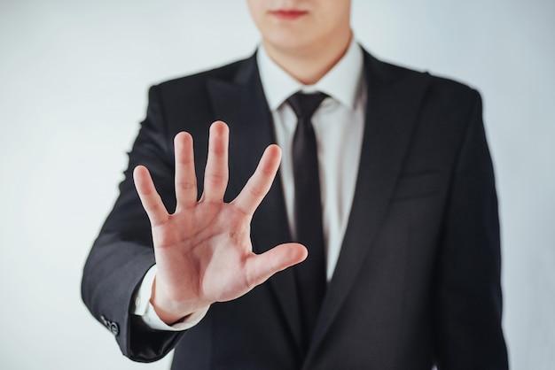 Joven empresario en un traje muestra su mano