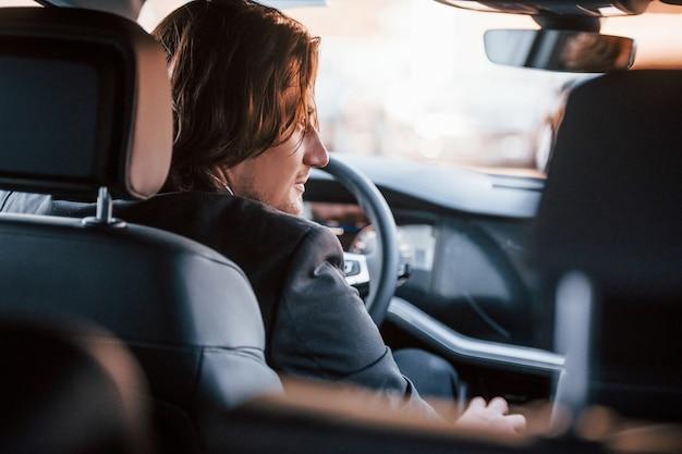 Joven empresario de traje negro y corbata conduciendo automóviles modernos.