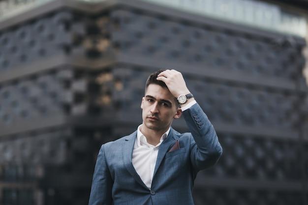 Joven empresario en traje de pie en la ciudad. hombre, llevando, reloj