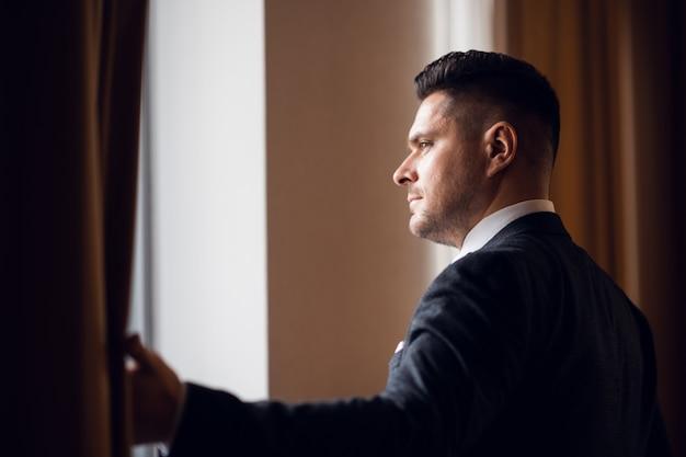 Un joven empresario en traje separando las cortinas de su habitación de hotel para dejar entrar la luz de la mañana