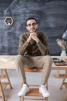 Joven empresario tranquilo en ropa casual mirándote mientras está sentado en la mesa de madera con los pies en la silla frente a la cámara