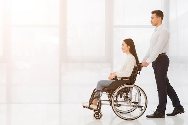 Joven empujando a la mujer discapacitada en silla de ruedas contra la ventana