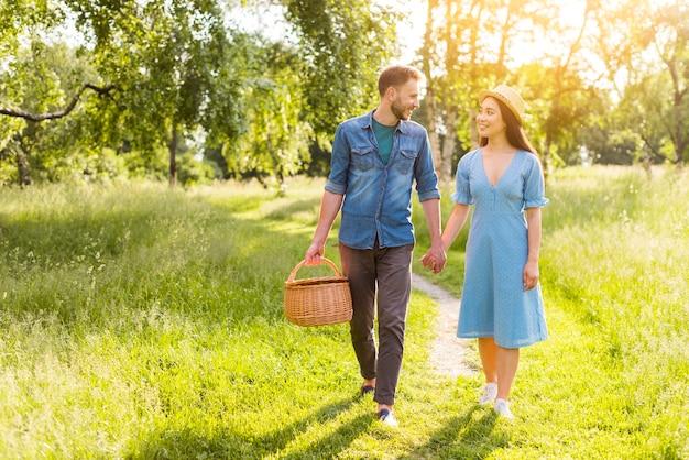 Joven enamorada multirracial caminando en el parque tomados de la mano