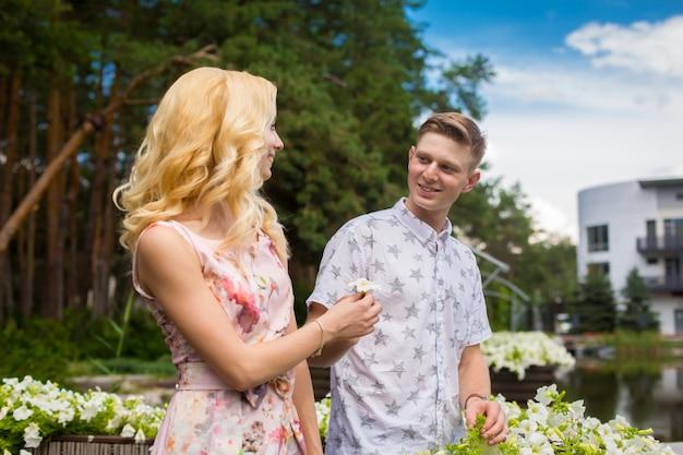 Joven encantadora chica rubia está coqueteando y con un chico en el jardín