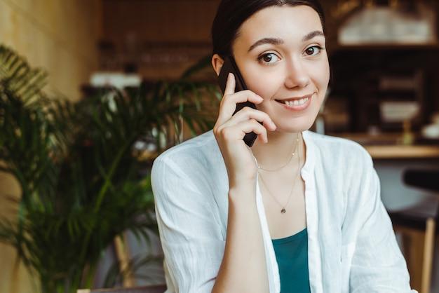 Joven encantadora llamada con teléfono celular, mientras está sentado solo en la cafetería.