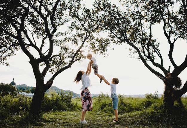 Una joven y encantadora madre abraza a sus pequeños hijos parados debajo