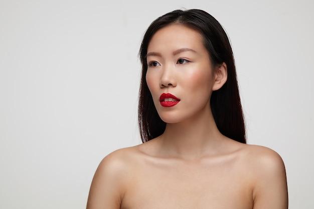 Joven encantadora mujer de cabello oscuro con maquillaje festivo mirando pensativamente a un lado mientras posa sobre una pared blanca con los hombros desnudos