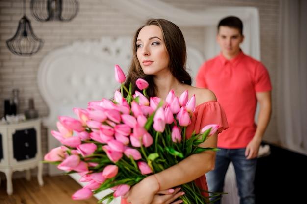 Joven y encantadora mujer con gran ramo de tulipanes
