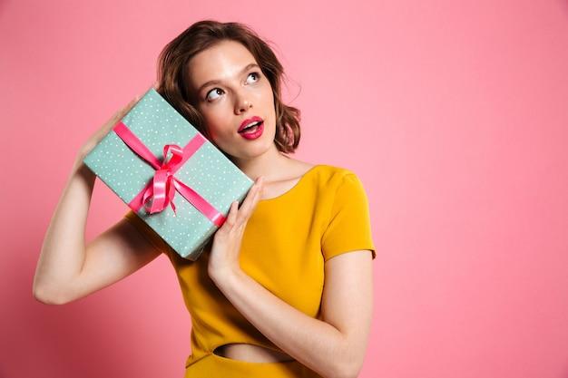Joven encantadora mujer en vestido amarillo con caja de regalo, mirando a un lado