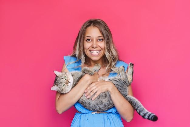 Una joven encantadora sostiene un gato en sus manos como un bebé aislado sobre un fondo de color rosa